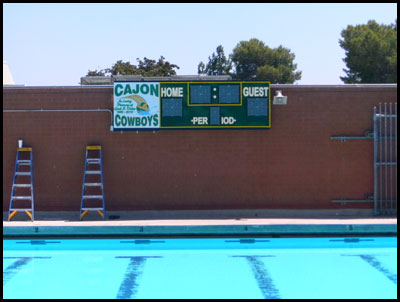 scoreboard marquee on brick building above lap pool