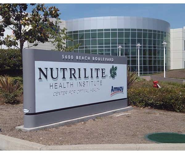 Modern looking grey and white sign with black raised lettering for Nutrilite Health Institute