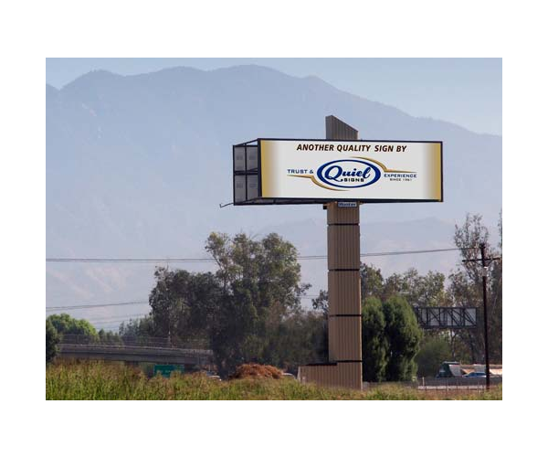 large billboard sign with quiel logo and mountains in the background