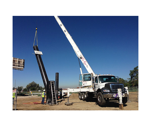 installers using crane to set a black pole for tall sign