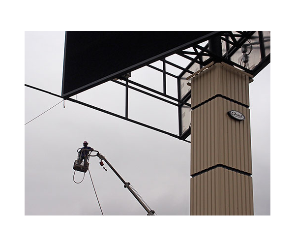 closeup of large LED billboard with installer in bucket lift next to sign