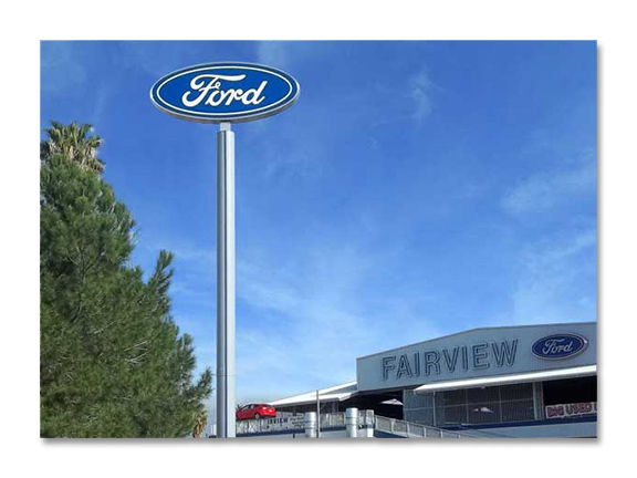 Ford logo on a tall blue sign against blue background