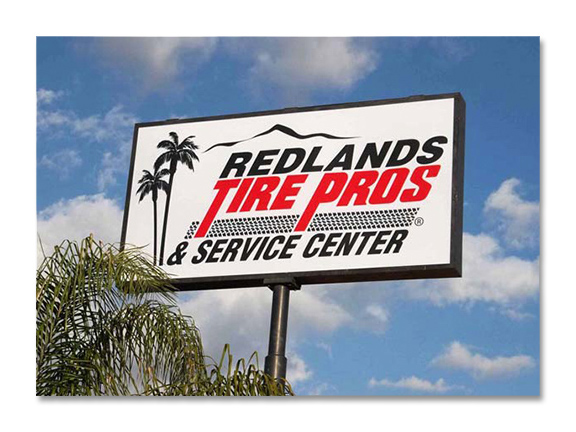 tall white and red sign against blue cloudy sky for Redlands Tire Pros and Service Center