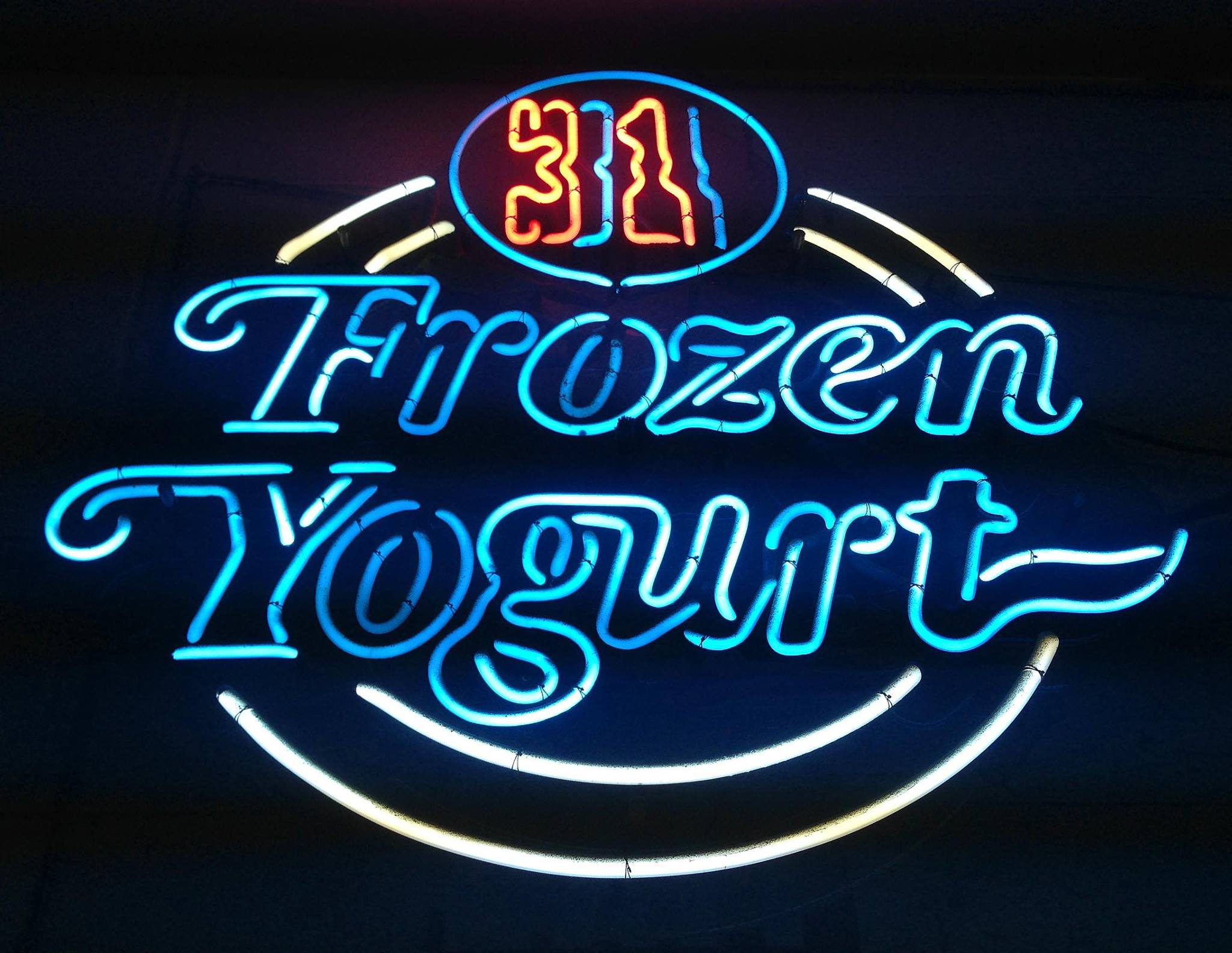 Frozen Yogurt white and blue neon sign against black background